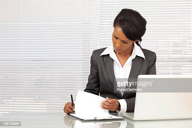 Businesswoman writing report at office