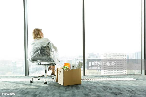 Businesswomanp on empty office floor with cardboard box looking out of window