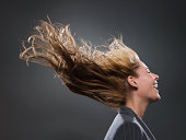 Businesswoman's hair blowing in wind