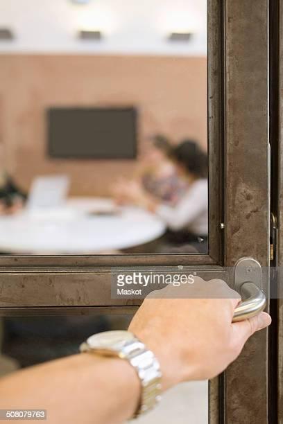 Businesswoman's hand opening door handle in creative office