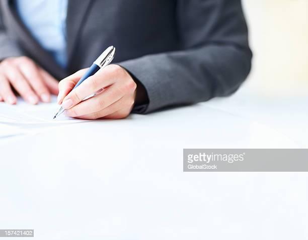 Mujer de negocios manos de firmar un contrato