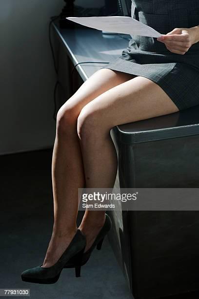 Businesswoman's legs dangling off desk