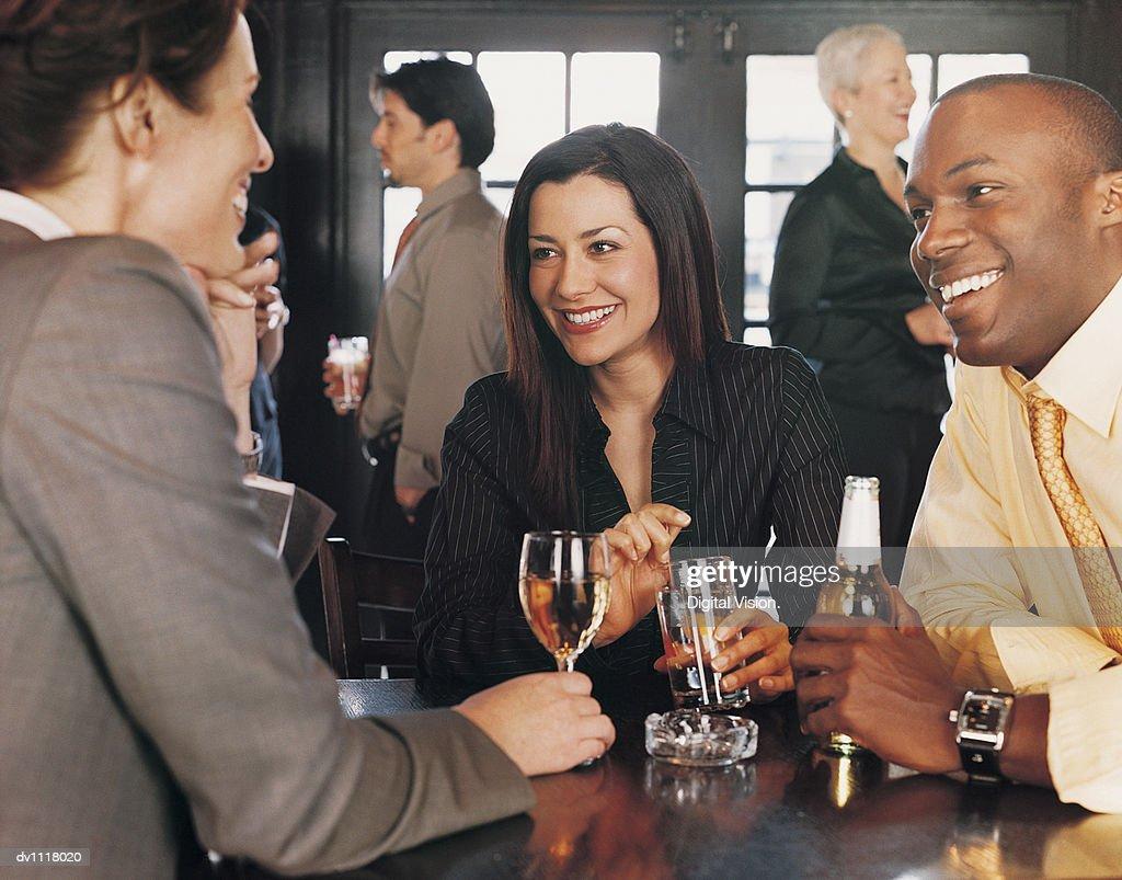 Businesswomen and a Businessmen Enjoying a Drink in a Pub