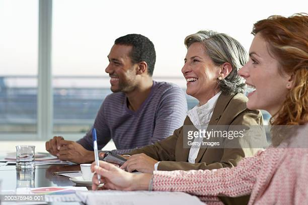 Businesswomen and man at table in meeting, smiling