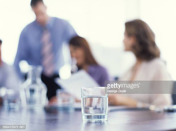 Businesswomen and man in office, glass of water on table