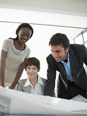 Businesswomen and man looking at plans on desk, low angle