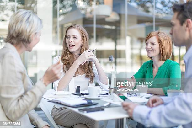 Businesswomen and man meeting at coffee break on hotel terrace