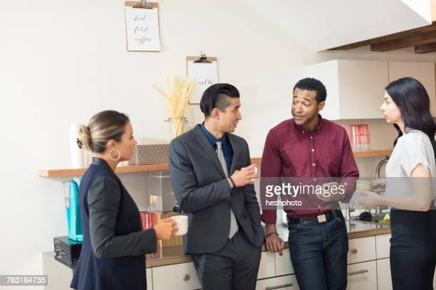 Businesswomen and men having informal meeting in office kitchen