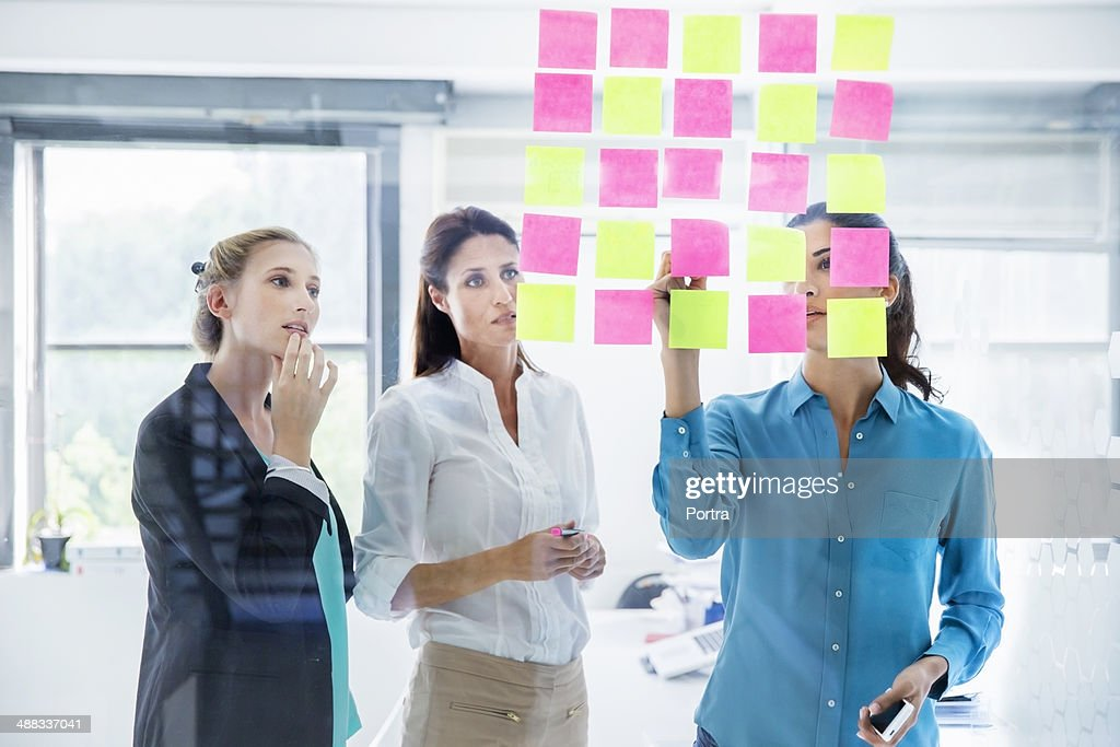 Businesswomen at the office writing down thoughts. : Stock Photo