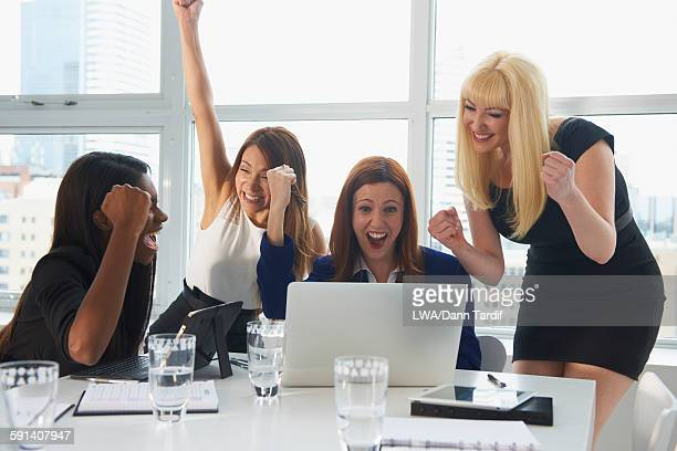 Businesswomen cheering at laptop in office meeting