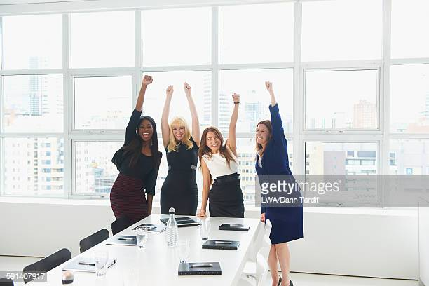 Businesswomen cheering in conference room