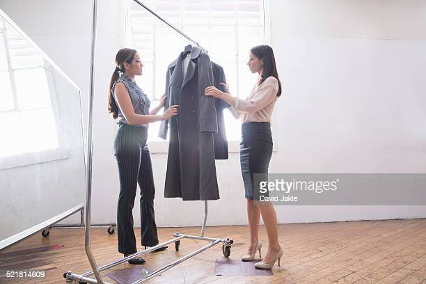 Businesswomen choosing smart clothes from clothes rail