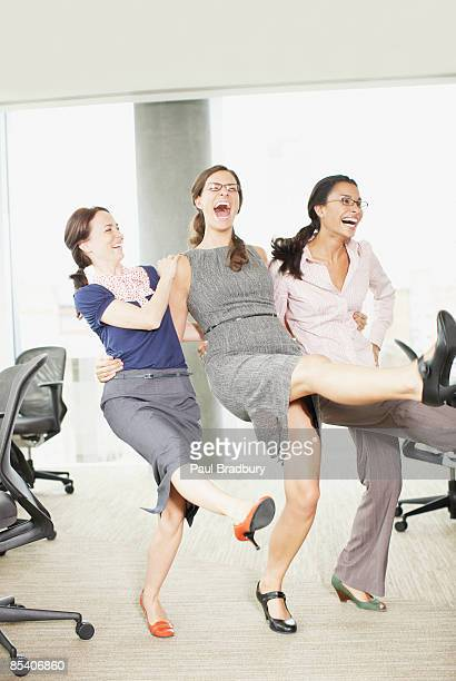 Businesswomen dancing in office