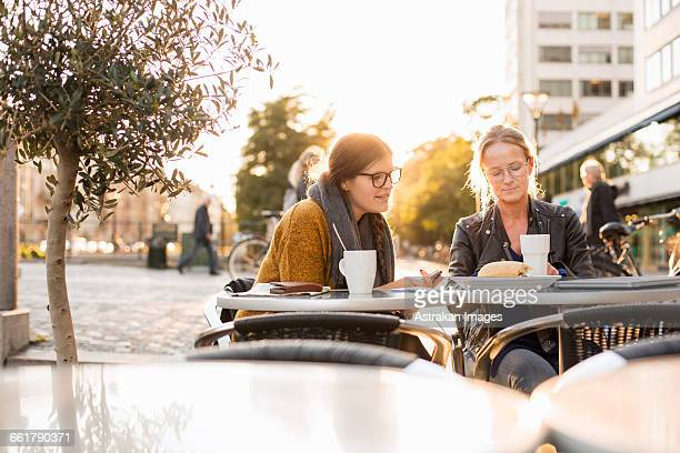 Businesswomen discussing on table at sidewalk cafe