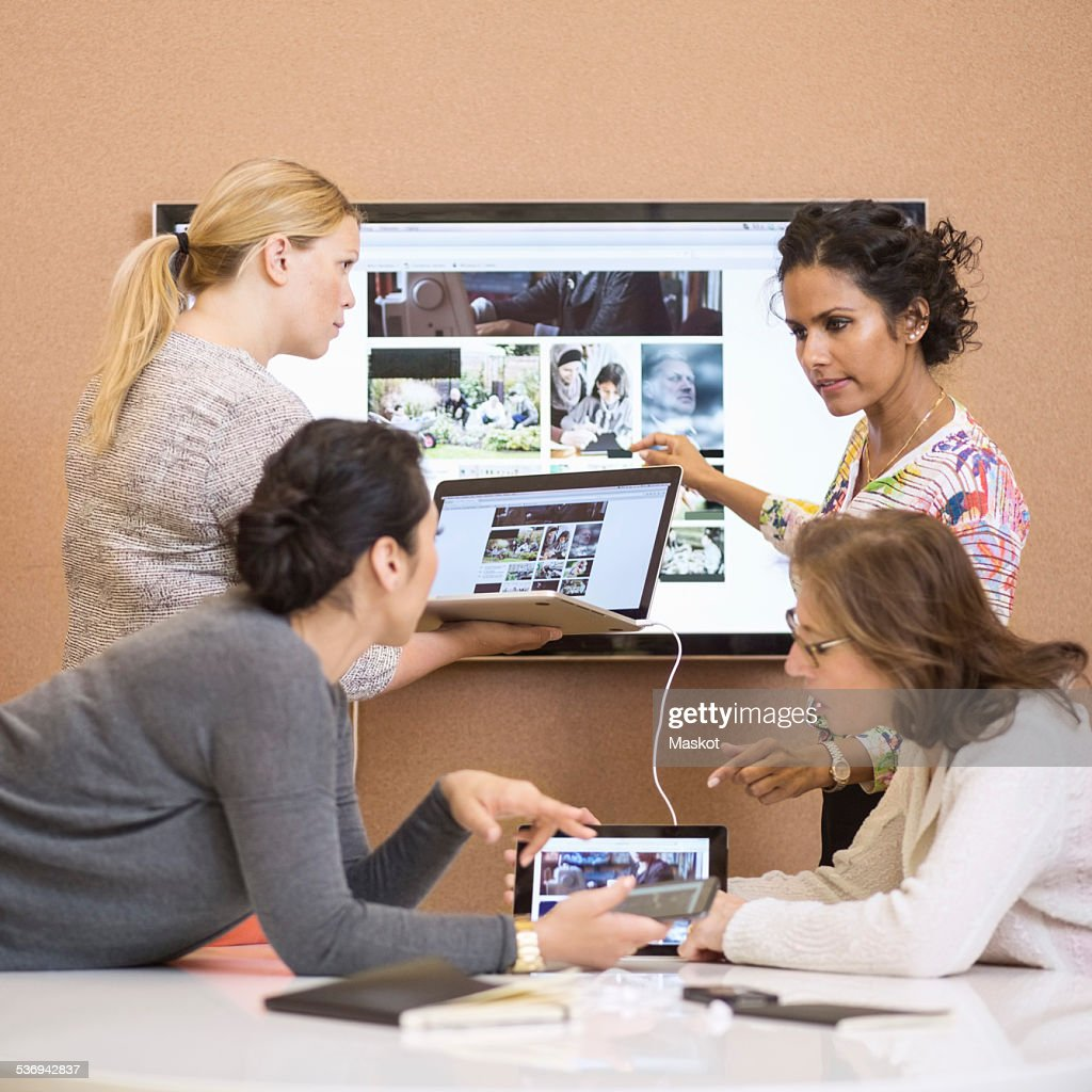 Businesswomen discussing presentation in creative office