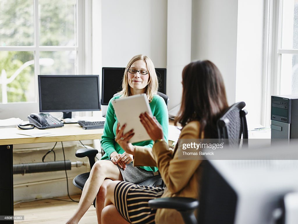 Businesswomen discussing project on digital tablet : Stock Photo