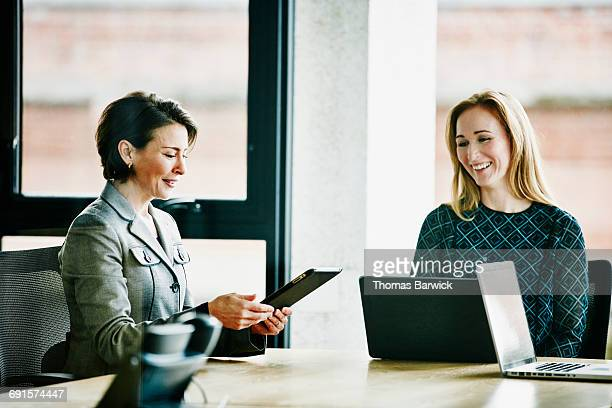 Businesswomen discussing project on digital tablet