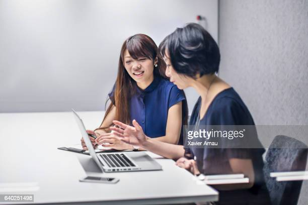 Businesswomen discussing project on laptop