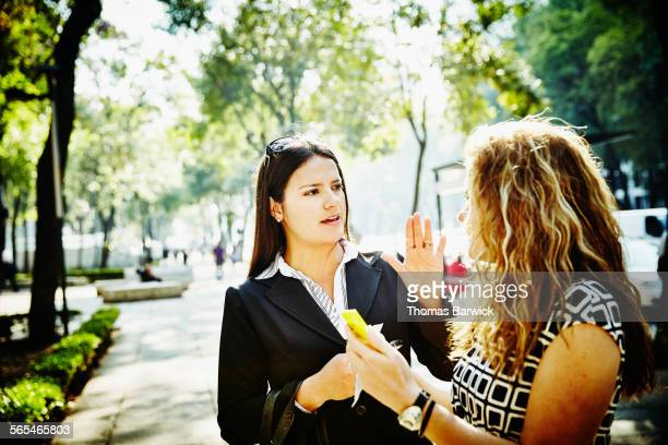 Businesswomen discussing project on sidewalk