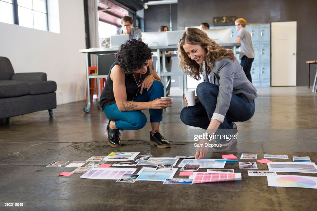 Businesswomen examining paperwork on office floor : Stock Photo