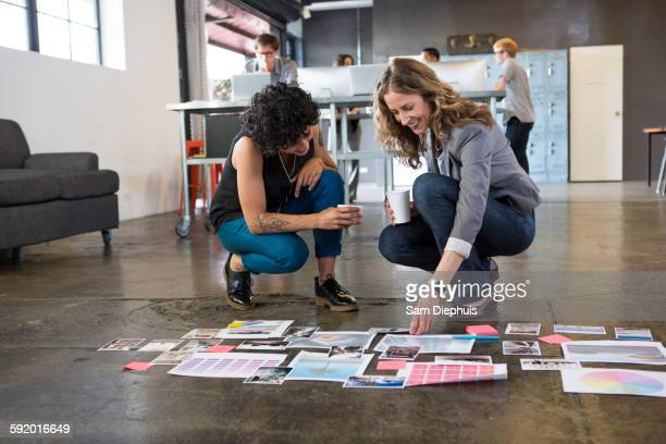 Businesswomen examining paperwork on office floor