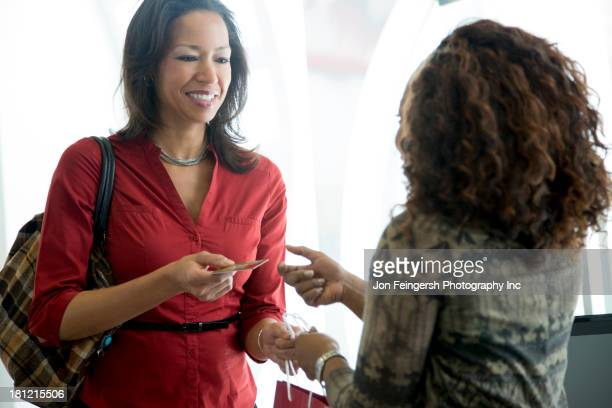 Businesswomen exchanging business cards