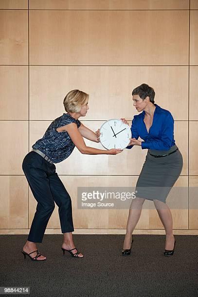 Businesswomen fighting over clock