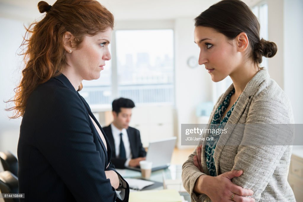 Businesswomen glaring at each other in office : Stock Photo