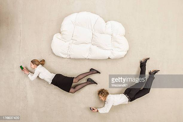 Businesswomen holding mobile phone and flying below cloud shape pillow