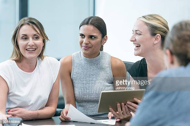 Businesswomen in meeting laughing with digital tablet