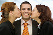 Businesswomen Kissing Businessman's Cheeks