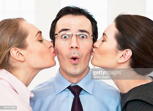 Businesswomen kissing colleagues cheeks