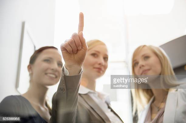 Businesswomen looking and pointing on glass