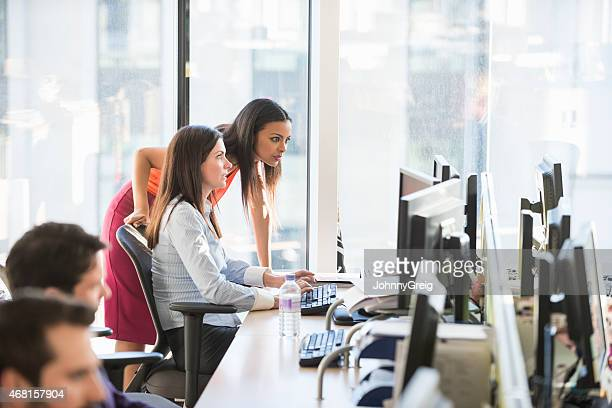 Businesswomen looking at computer at desk