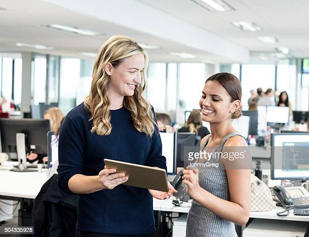 Businesswomen looking at digital tablet in modern office, smiling
