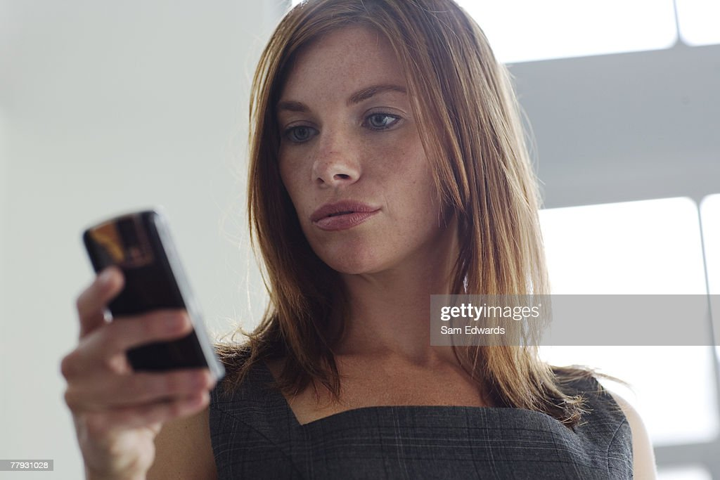 Businesswomen looking at her cellular phone indoors : Stock Photo