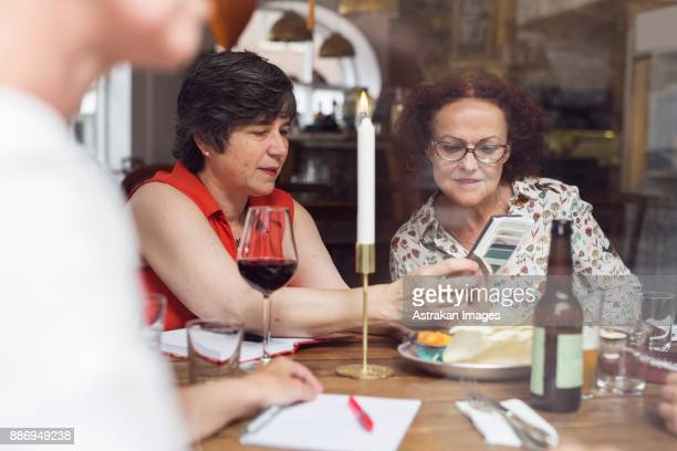 Businesswomen looking at mobile phone during lunch in restaurant