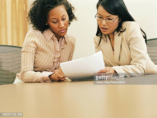 Businesswomen looking at papers in conference room