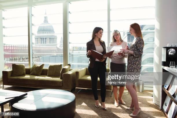 Businesswomen meeting by office sofa, London, UK