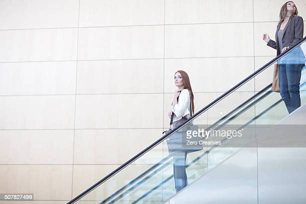 Businesswomen moving down on conference centre elevator