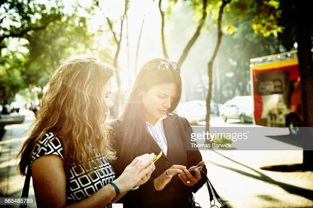 Businesswomen on city sidewalk using smartphones