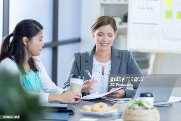 Businesswomen review documents during breakfast meeting