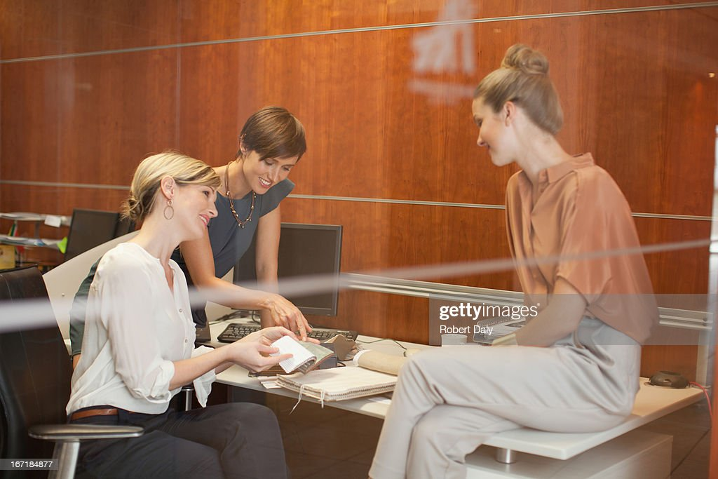 Businesswomen reviewing paperwork in office : Stock Photo