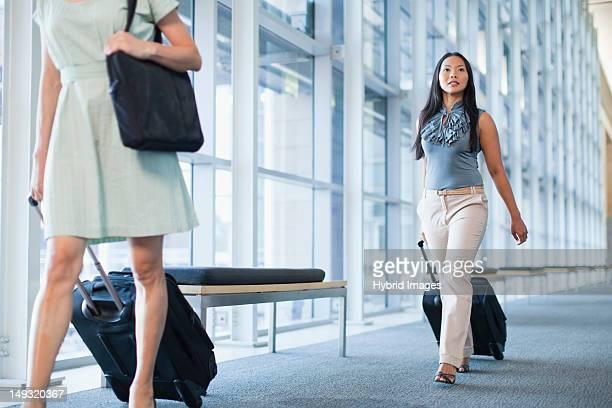 Businesswomen rolling luggage in hallway