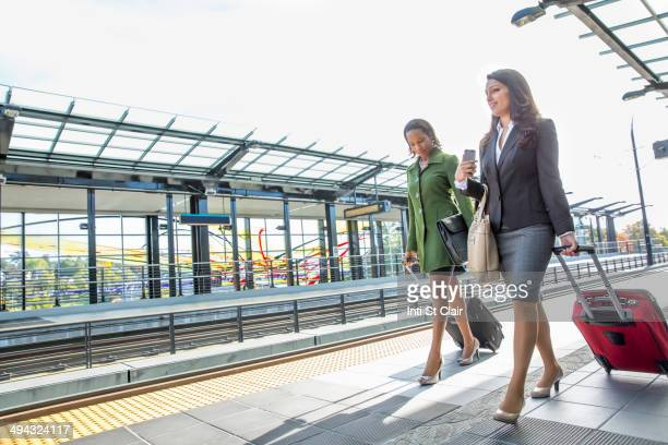 Businesswomen rolling luggage on train platform