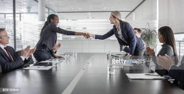 Femmes chefs d'entreprise se serrant la main après la signature du contrat