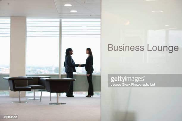 Businesswomen shaking hands in business lounge