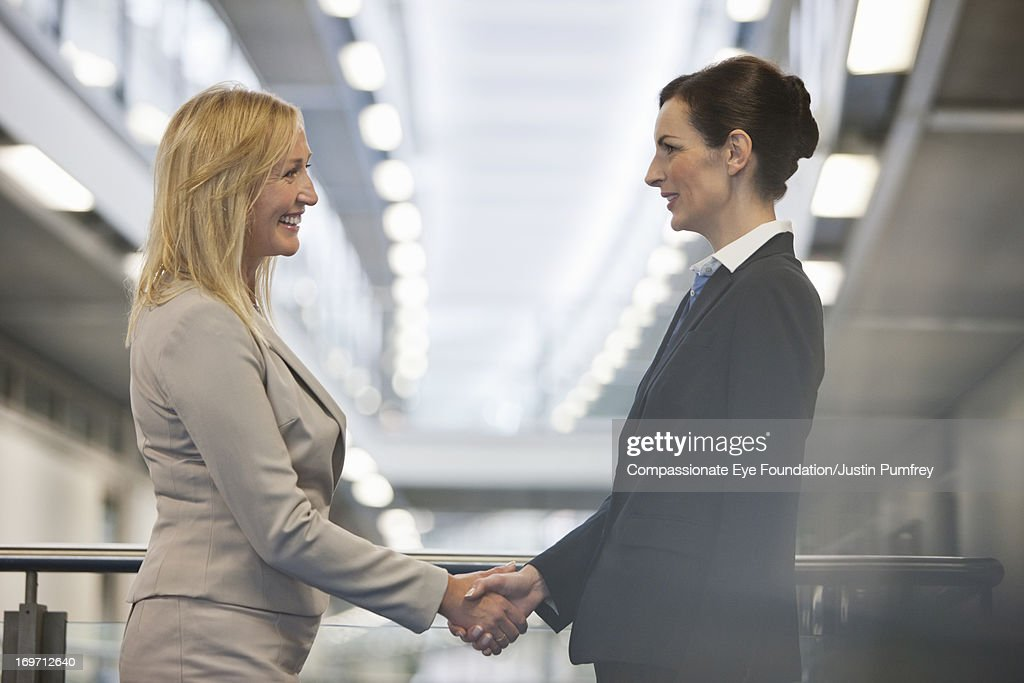 Businesswomen shaking hands in office hallway : Stock Photo