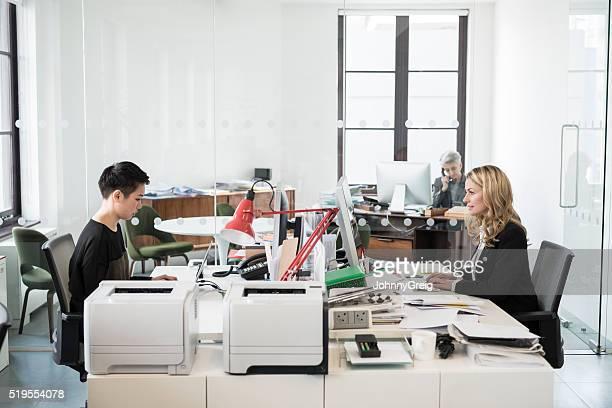 Businesswomen sitting at desk in modern office using computers
