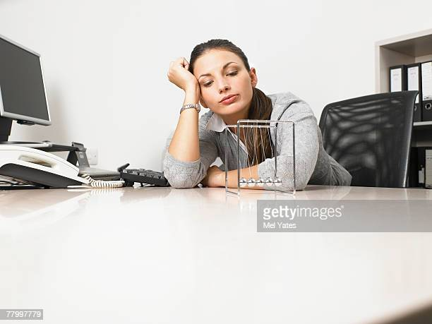 Businesswomen sitting at her desk with a Newton's Cradle